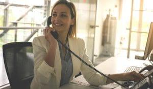 Business woman working in office. Woman talking on Landline phone.