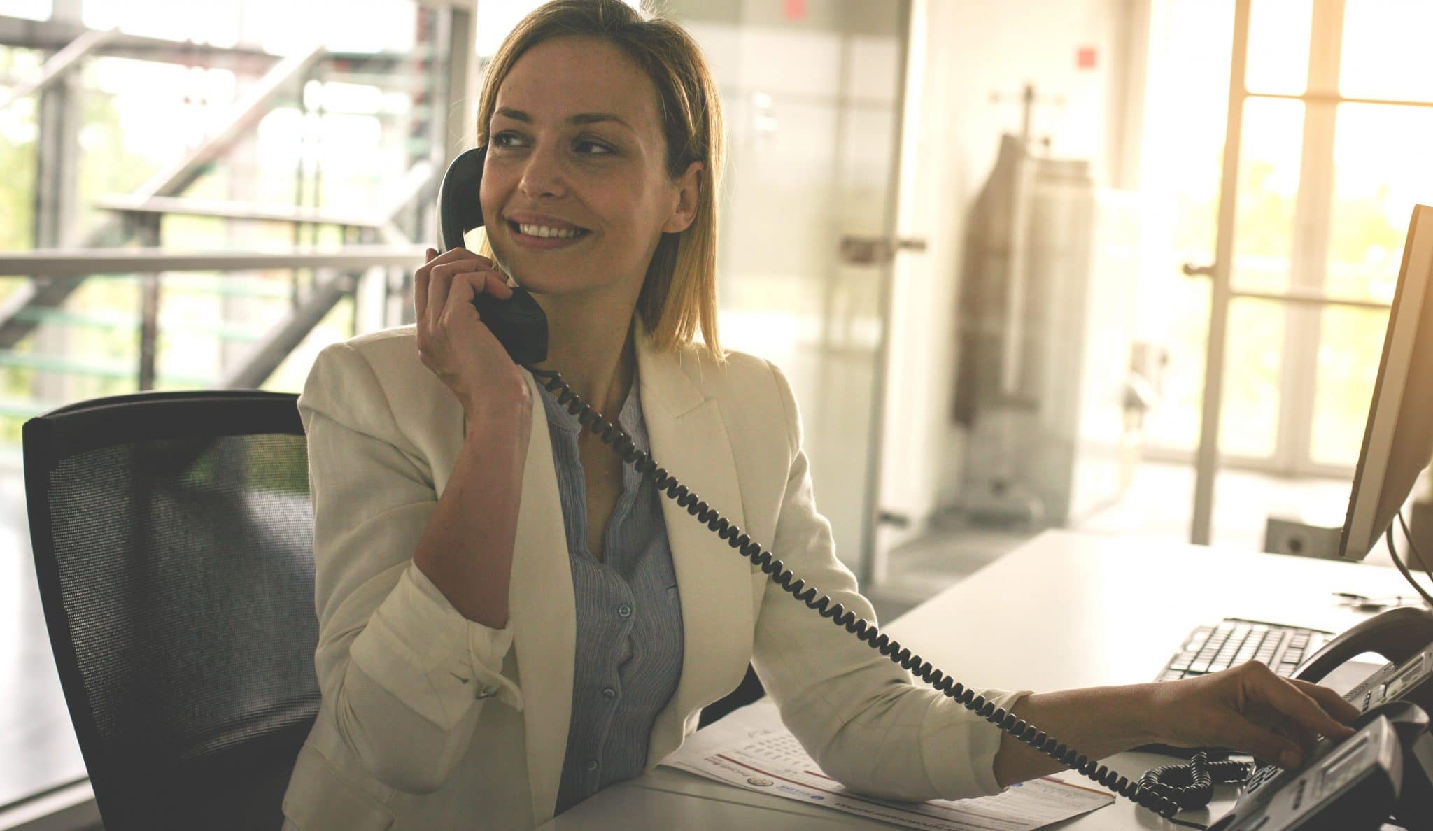 Business woman working in office. Woman talking on Landline phone.